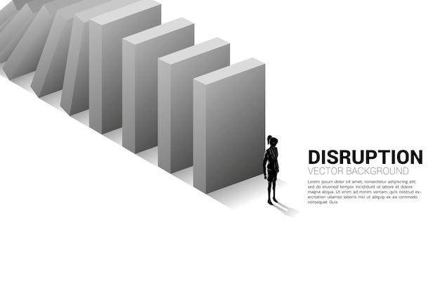 Silhouet van onderneemster die zich aan het eind van de domino-instorting bevindt