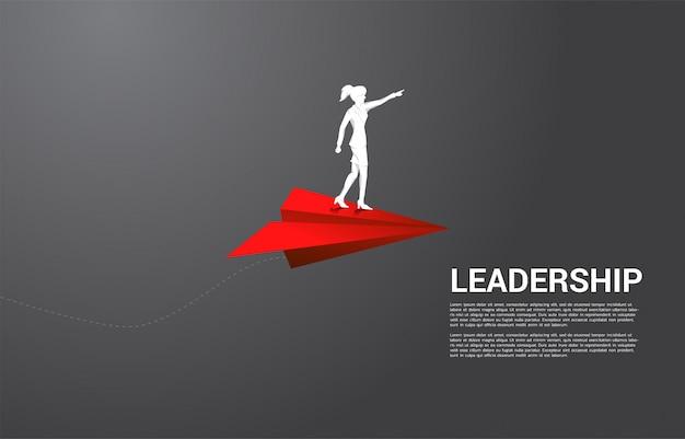 Silhouet van onderneemster die zich op rood origamidocument vliegtuig bevinden. bedrijfsconcept leiding, startbedrijf en ondernemer