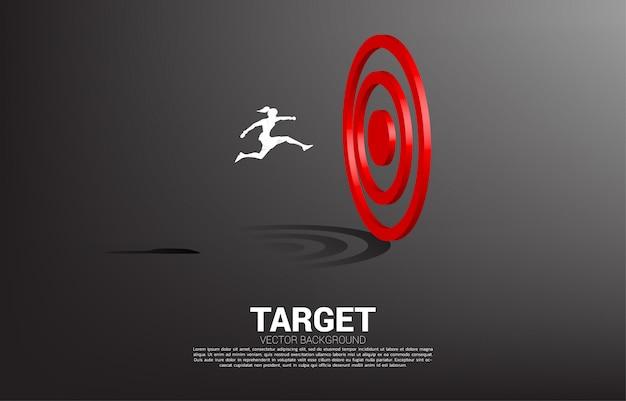 Silhouet van onderneemstersprong om dartboard te richten. concept van visie missie en doel van het bedrijfsleven