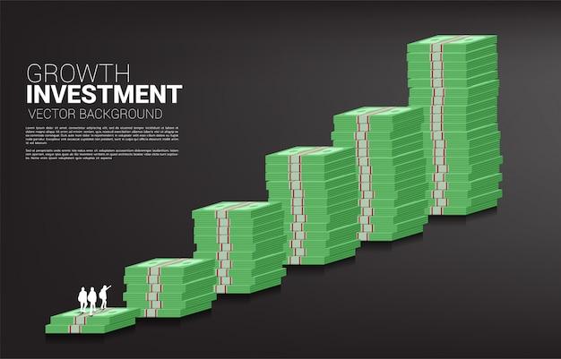 Silhouet van team dat omhoog aan bovenkant van stapel van bankbiljet kijkt.