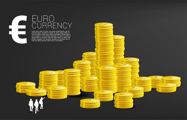 Silhouet van team die tot bovenkant van stapel van euro muntmuntstuk kijken