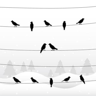 Silhouet van vogels op draden in winter achtergrond