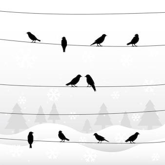 Silhouet van vogels op draden in winterseizoen