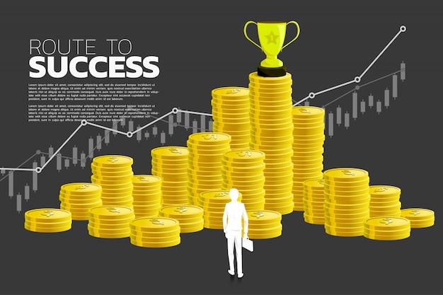 Silhouet van zakenman die aan de toekenning van de trofeekop op stapel van muntstuk kijkt.