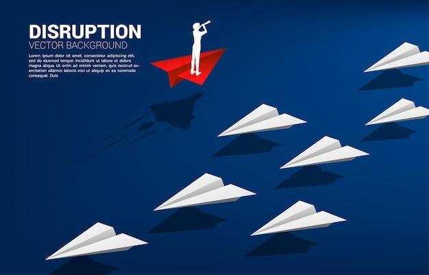 Silhouet van zakenman die door een telescoop kijkt die op een rood origami-papieren vliegtuigje staat, gaat op een andere manier dan de groep wit. bedrijfsconcept van disruptie en visiemissie.