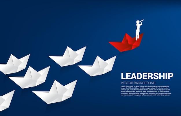 Silhouet van zakenman die door een telescoop kijkt op een rood origami-papieren schip dat het wit leidt. businessconcept van leiderschap en visie missie.