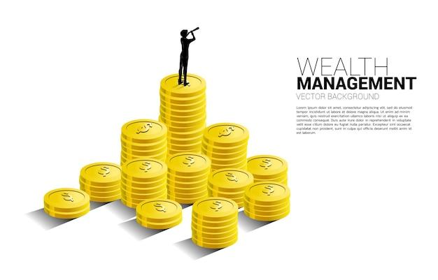 Silhouet van zakenman die door telescoop kijkt die zich bovenop stapel muntstuk bevindt. concept van succesinvesteringen en groei in het bedrijfsleven.