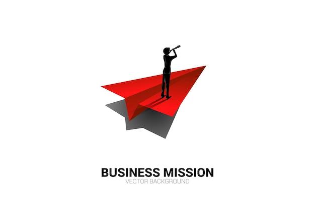 Silhouet van zakenman die door telescoop op origami papieren vliegtuigje kijkt. businessconcept van leiderschap en visie missie.