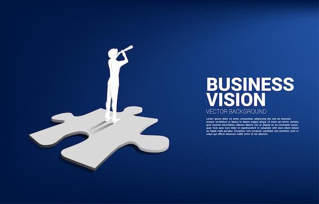Silhouet van zakenman die door telescoop op puzzelstukje kijkt. bedrijfsconcept voor missie en het vinden van een nieuw doelwit.