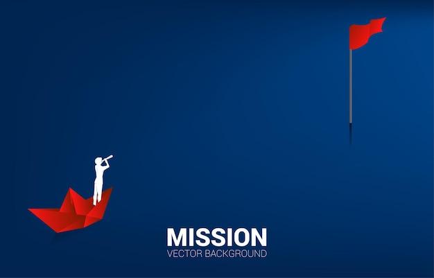 Silhouet van zakenman die door telescoop op rood origamidocument schip naar rode vlagdoel kijkt. businessconcept van leiderschap en visie missie.