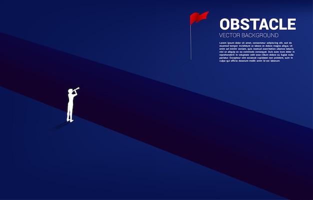 Silhouet van zakenman die door telescoop over afgrond naar doelvlag kijkt. bedrijfsconcept voor missie en het vinden van een nieuw doelwit.