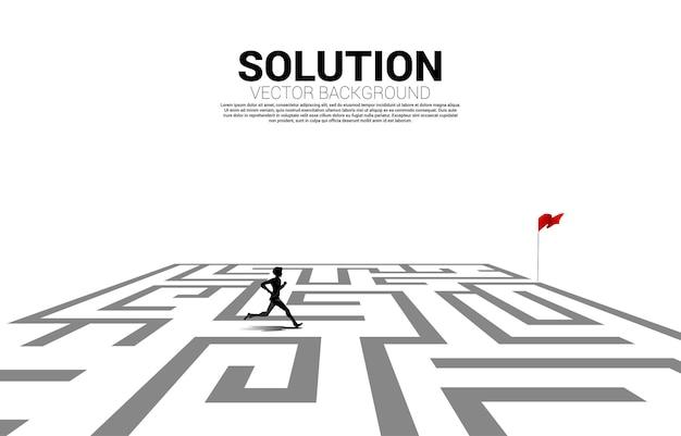 Silhouet van zakenman die in doolhof naar rode vlag loopt. bedrijfsconcept voor het vinden van een oplossing en het bereiken van het doel