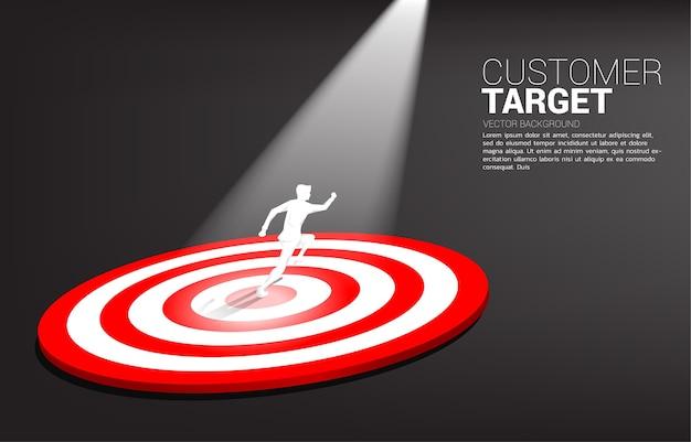 Silhouet van zakenman die op centrum van dartbord met vleklicht loopt. bedrijfsconcept van marketingdoel en klant.