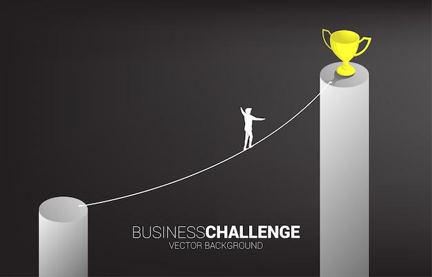 Silhouet van zakenman die op de manier van de kabelgang aan gouden trofee op hogere grafiek lopen