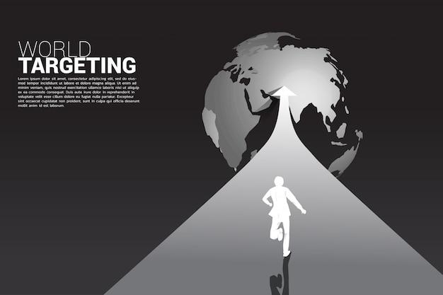 Silhouet van zakenman die op pijl aan wereldbol loopt.