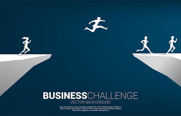 Silhouet van zakenman die over het hiaat van vallei met stadsachtergrond springt. concept van zakelijke uitdaging risico.