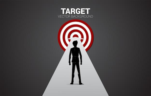 Silhouet van zakenman die zich op weg bevindt om dartboard te centreren. businessconcept van route naar doel en direct naar doel.