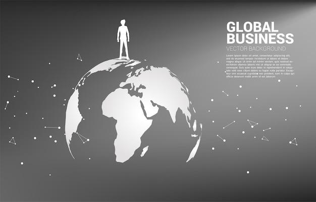 Silhouet van zakenman die zich op wereldbol bevindt.