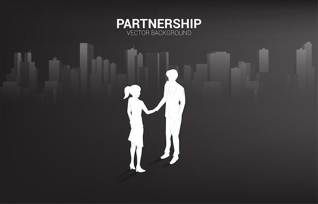 Silhouet van zakenman en zakenvrouw handdruk met stad achtergrond. concept van teamwork partnerschap en samenwerking.