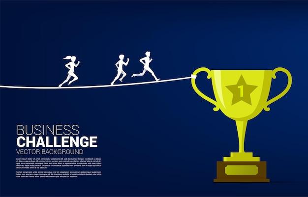 Silhouet van zakenman en zakenvrouw lopen op touw lopen weg naar gouden trofee. concept voor zakelijke risico's en uitdaging.