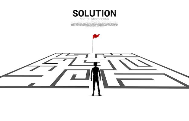 Silhouet van zakenman gaat naar het doolhof naar de rode vlag. bedrijfsconcept voor het vinden van een oplossing en het bereiken van het doel