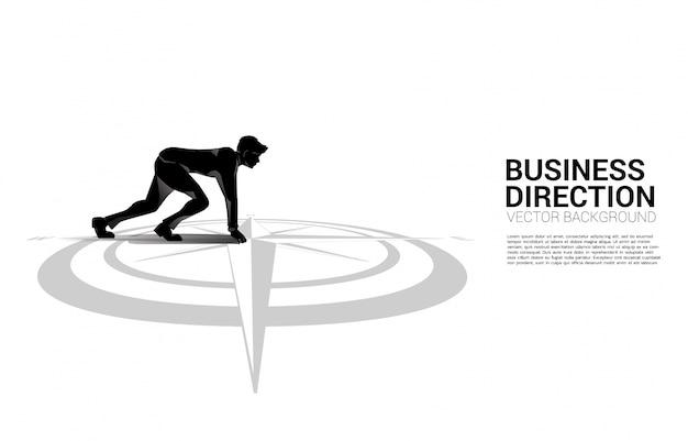 Silhouet van zakenman klaar om van centrum van kompas op vloer te lopen.