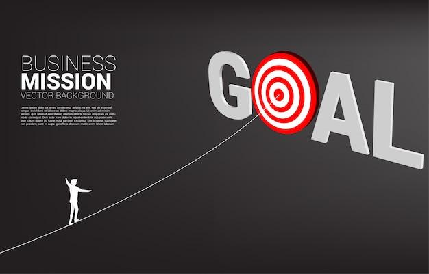 Silhouet van zakenman lopen touw naar het midden van het doel. concept van targeting en zakelijke uitdaging.