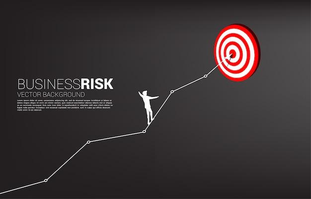 Silhouet van zakenman lopen touw online grafiek naar midden van dartbord sjabloon