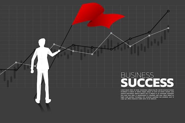 Silhouet van zakenman met de rode vlag die zich met de groeigrafiek bevindt.