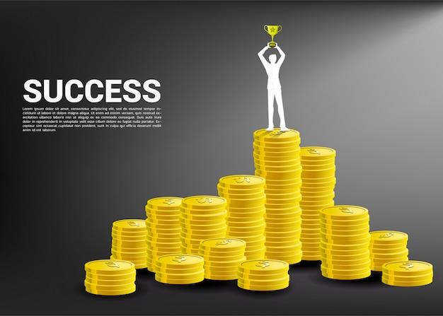 Silhouet van zakenman met trofeekop bovenop stapel van muntstuk