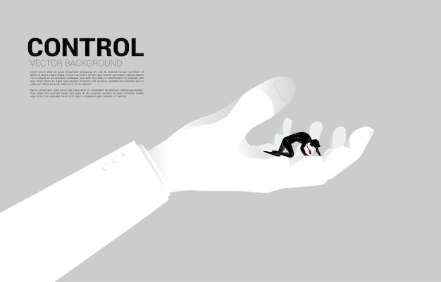 Silhouet van zakenman op knie in grote hand. concept voor het werkleven in controle.