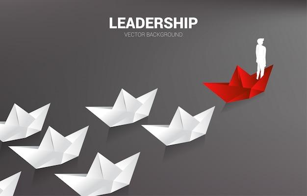 Silhouet van zakenman op rood origamidocument schip die het wit leiden.