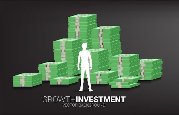 Silhouet van zakenman permanent bovenop en stapel bankbiljetten. concept van succesinvesteringen en groei in het bedrijfsleven