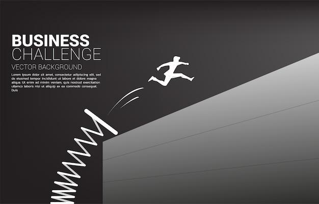 Silhouet van zakenman sprong over de muur met springplank