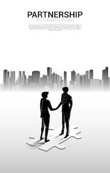 Silhouet van zakenmanhanddruk op figuurzaag met stadsachtergrond. concept van teamwork partnerschap en samenwerking.