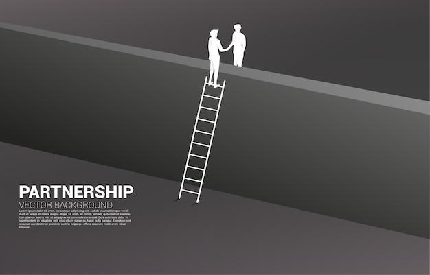 Silhouet van zakenmanhanddruk van over de muur. concept van teamwerkpartnerschap en succesovereenkomst.