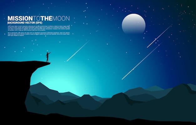 Silhouet van zakenmanpunt vooruit van bergklip naar de maan 's nachts. bedrijfsvisie missie en doel