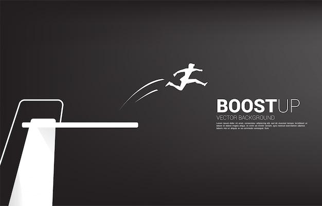 Silhouet van zakenmansprong hoger met springplank. concept van boost en groei in het bedrijfsleven.