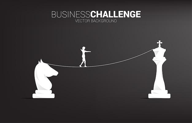 Silhouet van zakenvrouw lopen op touw lopen weg naar van ridder naar koning schaken. concept voor zakelijke uitdaging en strategie