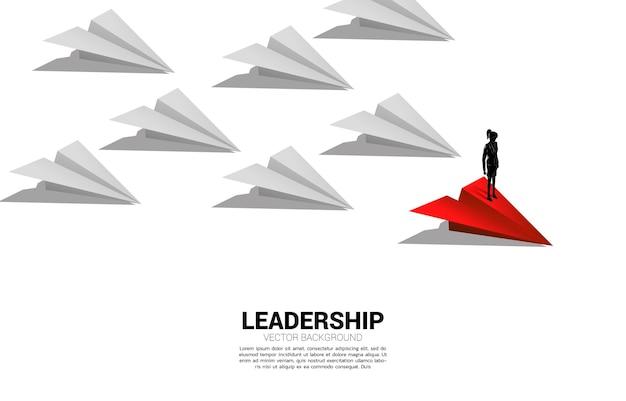 Silhouet van zakenvrouw staande op rode origami papieren vliegtuigje