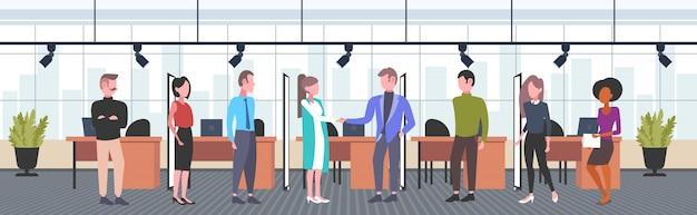 Slepen zakenpartners teamleiders handen schudden mannen vrouwen ondernemers overeenkomst partnerschap concept co-working open ruimte centrum modern kantoor interieur horizontaal volledige lengte