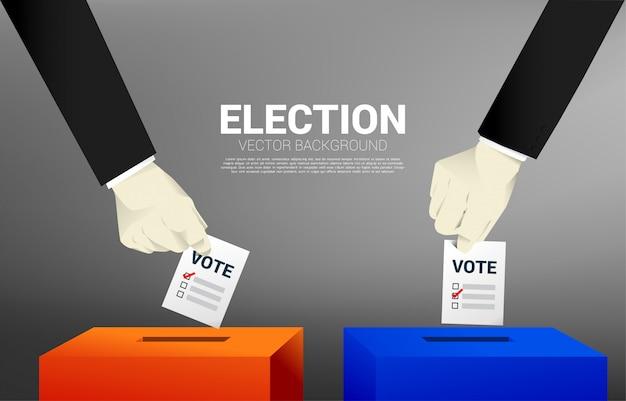 Sluit omhoog twee zakenmanhand zette zijn stem aan de rode en blauwe verkiezingsdoos.