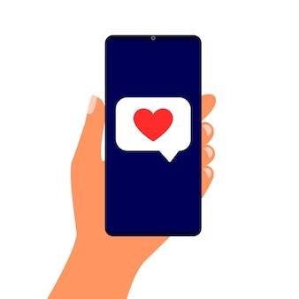Smartphone in de hand met de tekstballon van het rood hart. bericht op het scherm, zoals.