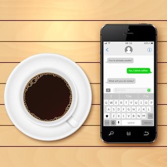 Smartphone met sms-chat en koffiekopje op houten tafel