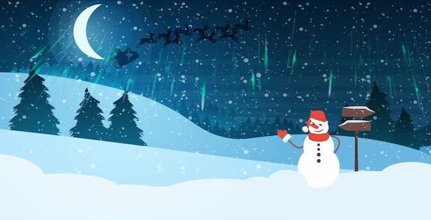 Sneeuwpop in hoed en sjaal zwaaien hand in nacht dennenbos santa vliegen in slee met rendieren in heldere sterrenhemel gelukkig nieuwjaar vrolijk kerstfeest illustratie