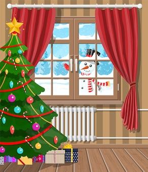 Sneeuwpop kijkt in het raam van de woonkamer. interieur van kamer met kerstboom en geschenken. gelukkig nieuwjaar decoratie. vrolijk kerstfeest. nieuwjaar en kerstmisviering.