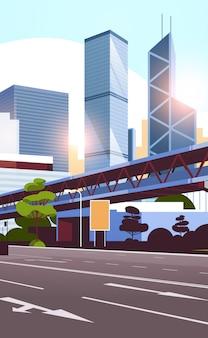Snelweg weg naar de skyline van de stad met moderne wolkenkrabbers en metro