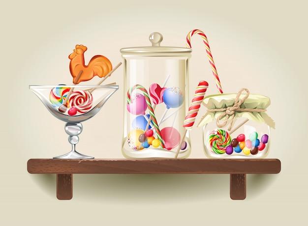Snoepjes in glazen potten op houten plank