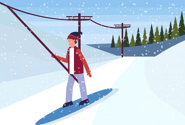 Snowboarder man glijdend van de berg met behulp van een skilift kabel