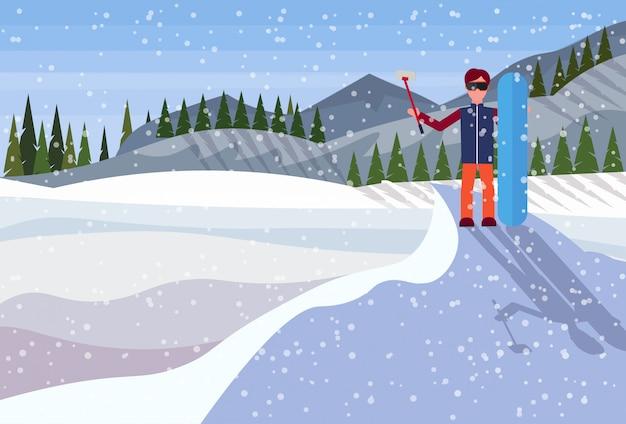 Snowboarder man houdt snowboard en neemt selfie